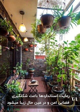 بالکنی پر از گلدان های گل روی زمین، دیوار و سقف با میز و صندلی چوبی