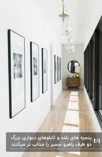 تابلوهای بزرگ روی دیوار راهرو رو به روی پنجره های بزرگ و آینه انتهای راهرو