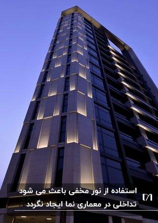نمای خاکستری آپارتمانی بلند با نورپردازی مخفی