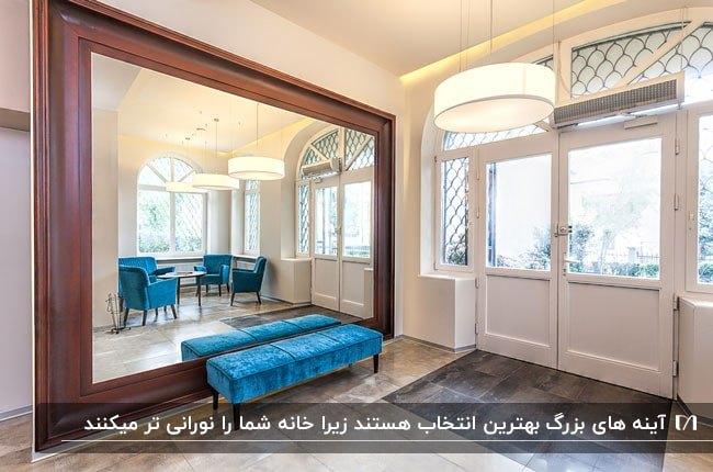ورودی بزرگی با یک آینه مستطیلی بزرگ با قاب چوبی و نیمکت مخمل آبی