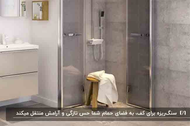 حمامی با دیوارهای بتنی خاکستری و کفپوش سنگ ریزه