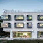 ساختمانی با نمای سیمان سفید و چنجره هایی متفاوت اما مدرن و شیک