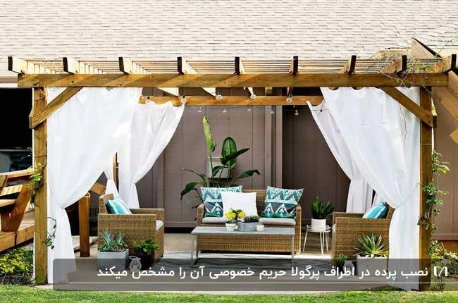 سایبان چوبی با پرده های سفید رنگ دور تا دورش ومبلمان حصیری به رنگ چوب