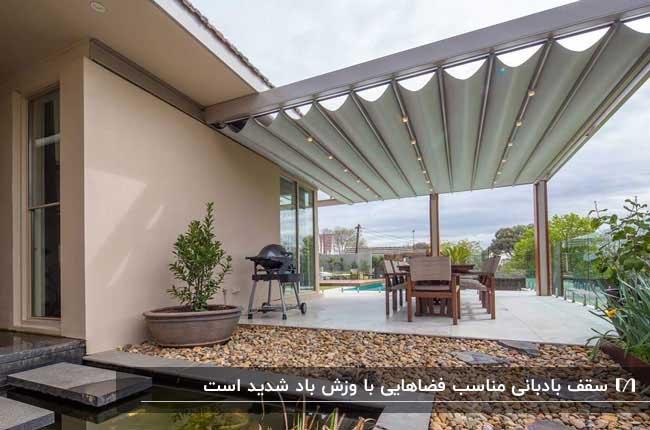 تصویری از یک پرگولا کنار سازه با سقف بادبانی سفید