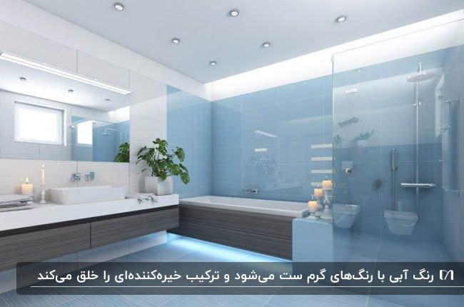 تصویر یک سرویس بهداشتی با کاشی های آبی رنگ و کابینت روشویی خاکستری