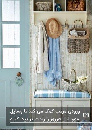 تصویر ورودی خانه ای با قفسه و جالباسی کرم رنگ و درب آبی آسمانی