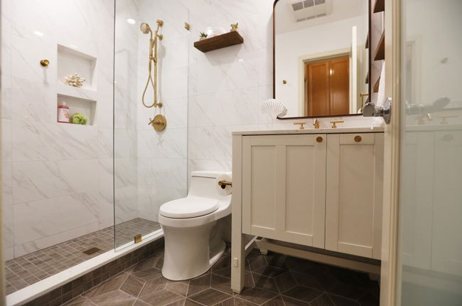 سرویس بهداشتی با کاشی های سفید و کابینت روشویی کرم و شیرآلات طلایی
