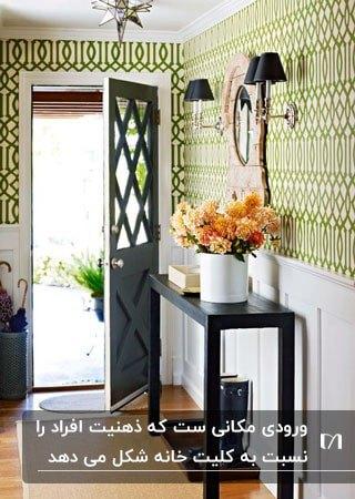 ورودی کوچکی با کاغذ دیواری سبز و سفید و کنسول مشکی