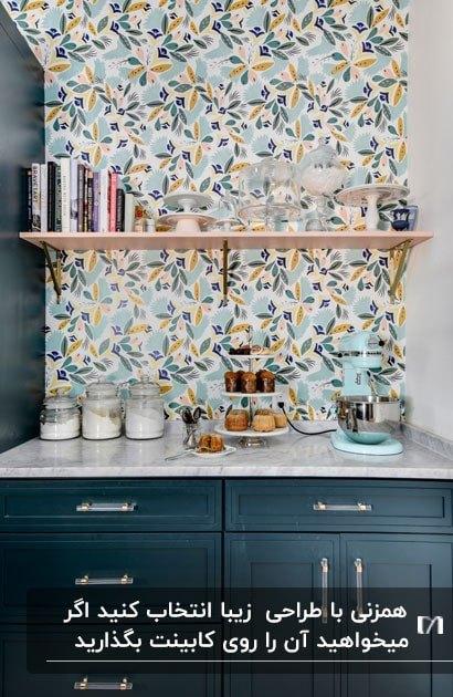 کنج یک آشپزخانه با کاغذ دیواری طرح دار یک قفسه چوبی روی دیوار و همزن آبی روی کانتر