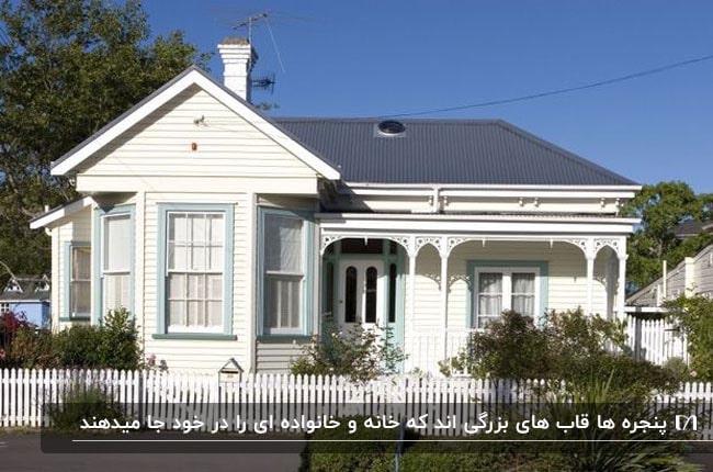 خانه ای با نمای سفید و آبی و پنجره هایی با فریم آبی آسمانی