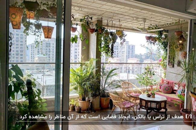 فضای سبز بالکنی بزرگ با صندلی های صورتی، میز قهوه ای و گلدان های گل روی دیوار و سقف