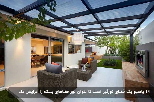 تصویر نورگیری با دو مبل حصیری تک نفره، شومینه و سقف نیمه شفاف