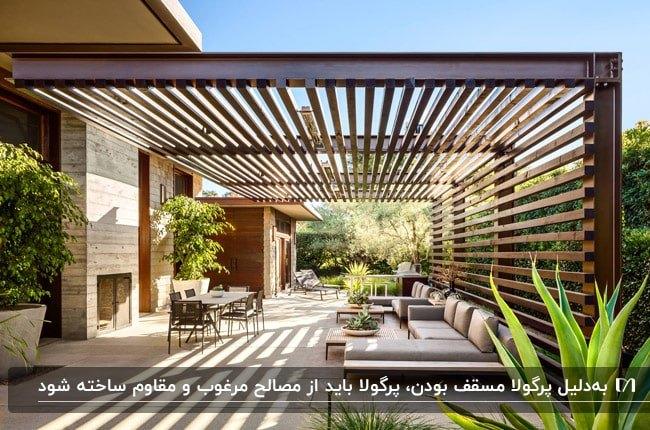 فضای باز خانه مدرن با یک پرگولای چوبی بزرگ و دو مبل ال شکل طوسی رنگ