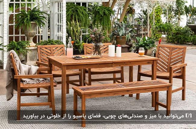 پاسیویی با میز و نیمکت و صندلی های چوبی و گیاهان بلند قد