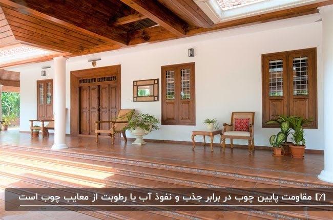 تصویری از ایوان خانه ای با درب و پنجره های چوبی و صندلی های چوبی