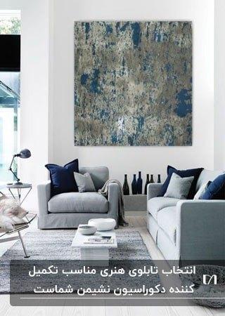 استفاده از یک تابلوی نقاشی بزرگ برای طراحی دیوار نشیمنی طوسی سرمه ای