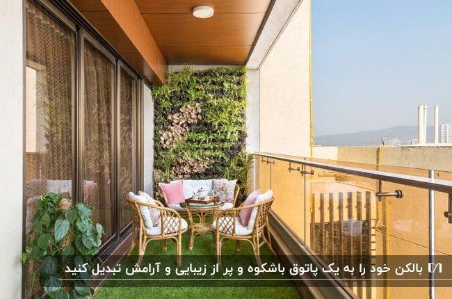 بالکنی با چمن مصنوعی، دیوار سبز و نرده های شیشه ای ومبلمان سفید صورتی