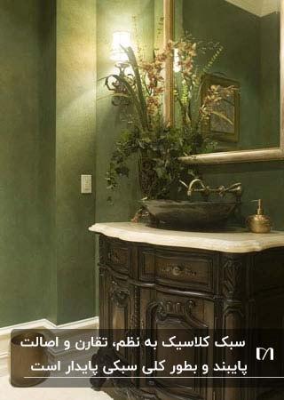 سرویس بهداشتی با دیوارهای سبز و کابینت روشویی چوبی