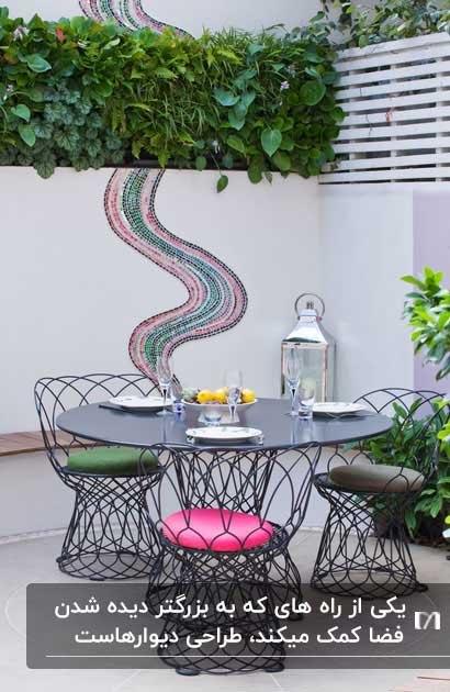 پاسیویی با میز و صندلی های فلزی و طراحی یکی از دیوارهای پاسیو