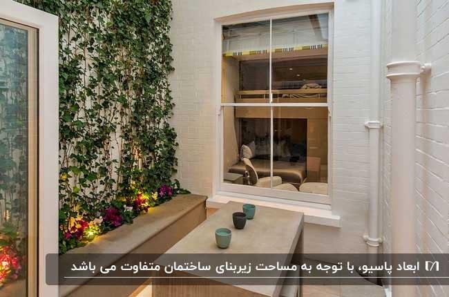 تصویر نورگیر کوچکی به رنگ سفید و کرم با باغچه و دیوارسبز با گیاهان رونده