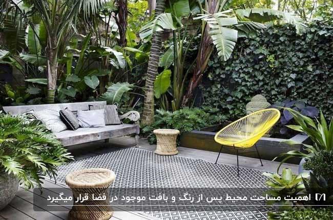 نورگیر سرسبزی با کاناپه طوسی و صندلی تک نفره فلزی زرد