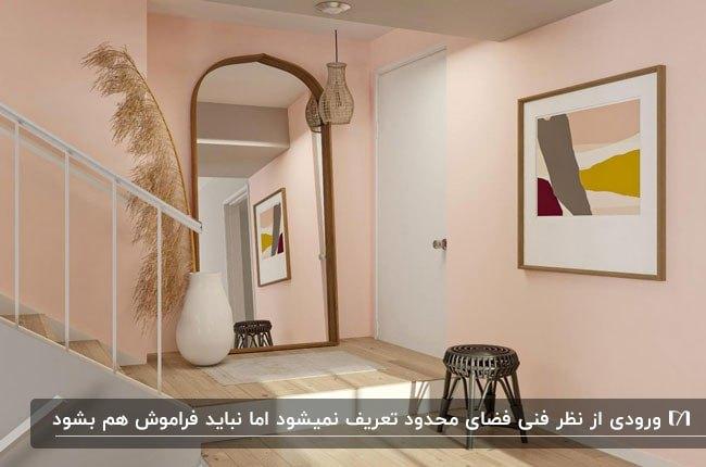 راهروی ورودی ای با دیوارهای صورتی و آینه نیم دایره بزرگ