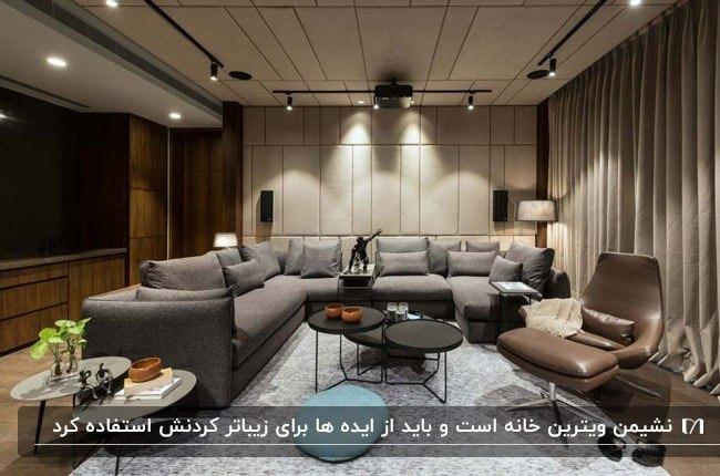 تصویر یک نشیمن با دیوارپوش ساده ای که تا سقف امتداد یافته است و مبلمان ال