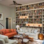 نشیمنی با مبلمان کرم و نارنجی با یک دیوار سرتاسر پوشانده شده با قفسه و دکوری