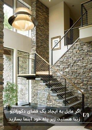 پله خانه ای با نرده های کابل و فلز و آبنمایی زیر راه پله روی دیوار سنگی