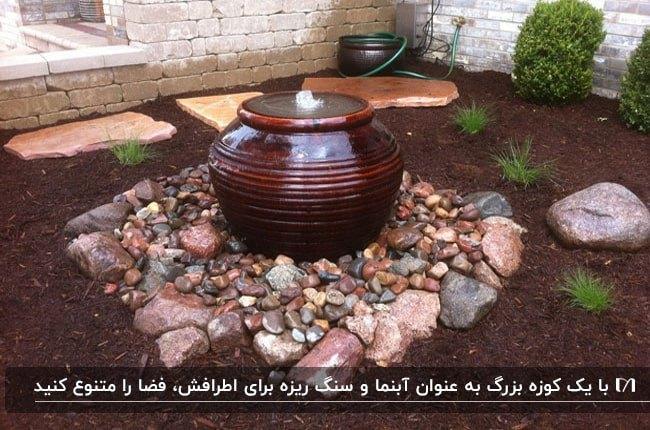 آبنمای کوزه ای قهوه ای رنگ با سنگ ریزه های اطرافش گوشه حیاط