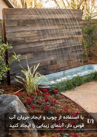 ساخت یک آبنمای ساده در فضای باغ با استفاده از چوب و ریزش آب قوس دار