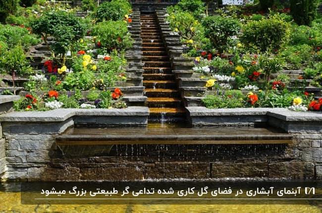 تصویر آبنمایی سنگی و آبشاری وسط یک فضایی کل گاری شده رنگارنگ