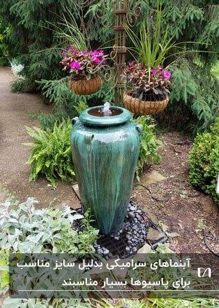 آبنمایی سرامیکی مشابه کوزه به رنگ سبز در فضای باغچه