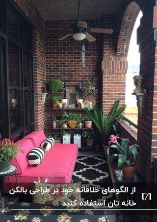 بالکنی با دیوارهای آجری، مبلمان صورتی و گلدان های گل