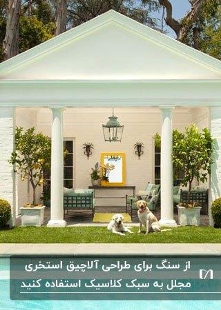 تصویری از یک آلاچیق کنار استخر به رنگ سفید و به سبک کلاسیک با دو سگ نشسته روی چمن حیاط