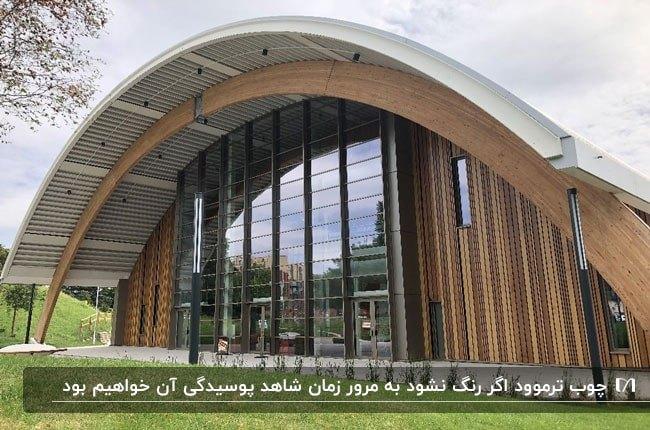 تصویری از یک ساختمان با معماری نیم دایره و نمای دو رنگ چوب ترموود