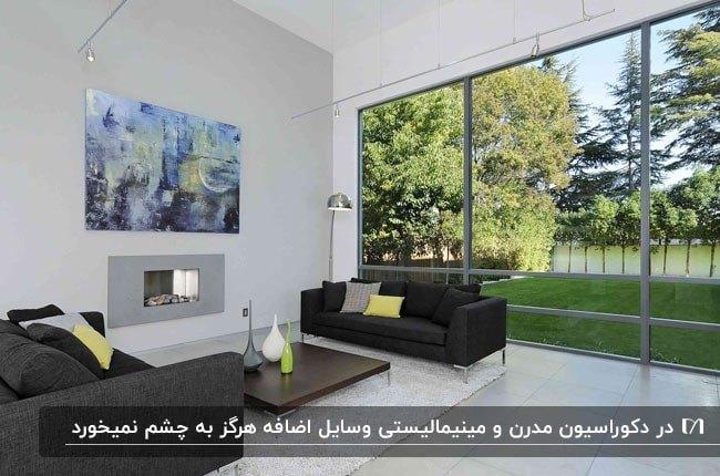 نشیمن مدرن و مینیمالی با مبلمان زغالی و تابلو روی دیوار کنار یک دیوار شیشه ای