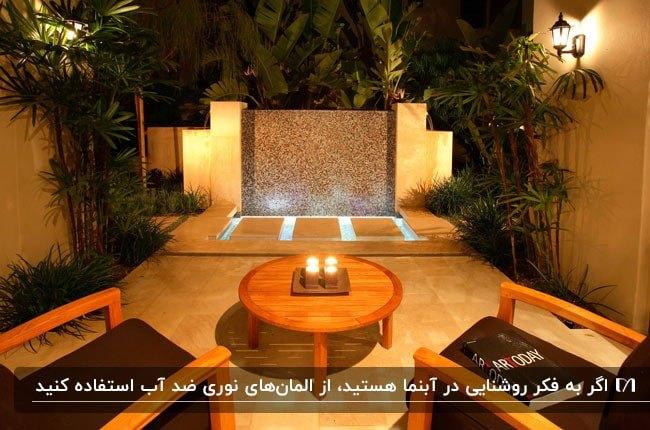 آبنمایی سنگی نورپردازی شده در حیاطی با میز گرد و صندلی های چوبی