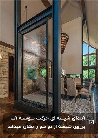 آبنمای شیشه ای در اتاق غذا خوری ای با سقف شیب دار بلند و کفپوش پارکت