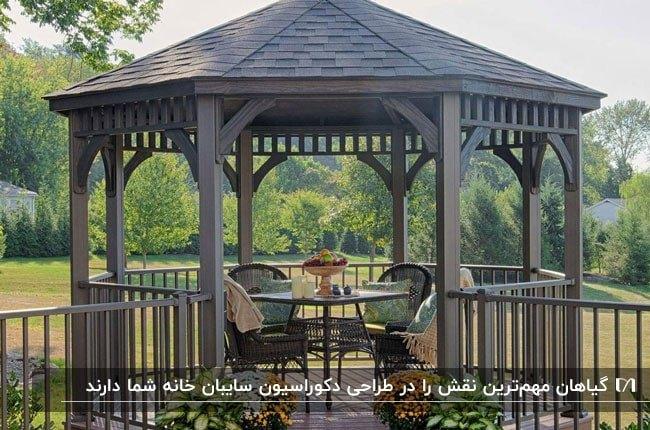 تصویر یک آلاچیق چوبی چندضلعی خاکستری با میز و چهار صندلی و گلدان های گل در ورودی