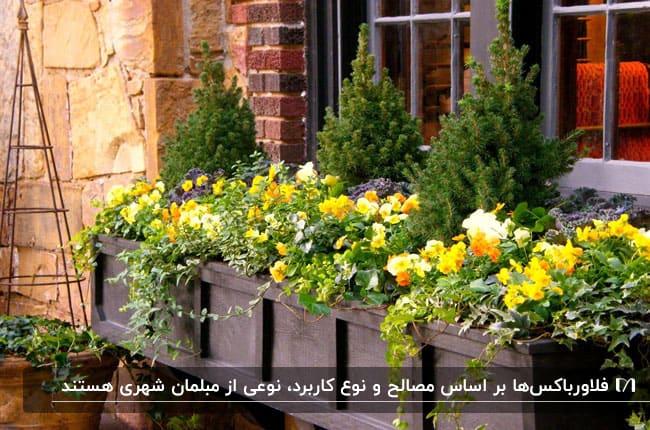 فلاورباکس چوبی جلوی پنجره به همراه گل های زرد و نارنجی و درختچه های کوچک
