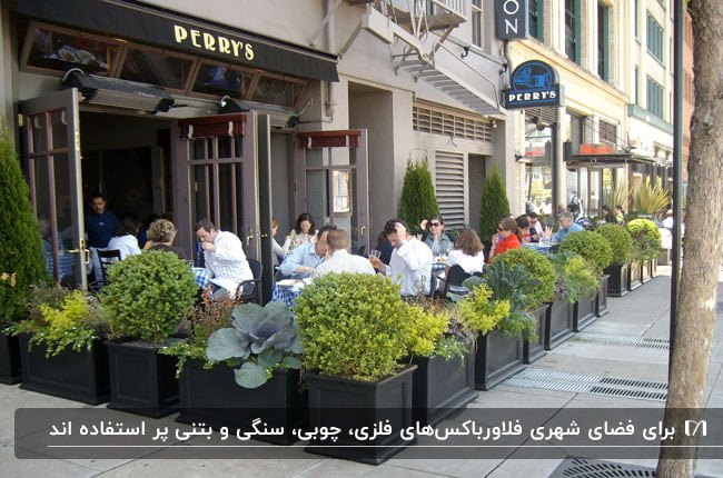 تصویری از یک رستوران خیابانی که با فلاورباکس های مشکی فضا را محصور کرده است