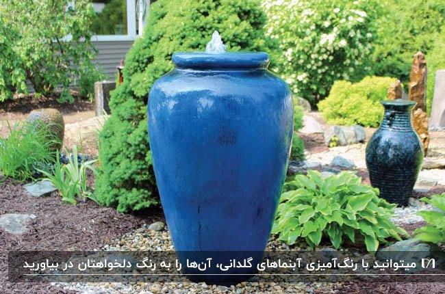 باغی با آبنمای گلدانی به رنگ های آبی و سرمه ای و گیاهان طبیعی بین گلدان ها