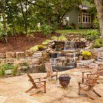 آبنمایی آبشاری و سنگی برای حیاط باغی بزرگ با صندلی های چوبی
