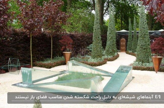 حیاط بزرگ و سرسبزی با آبنمای حیاطی شیشه ای مثلثی