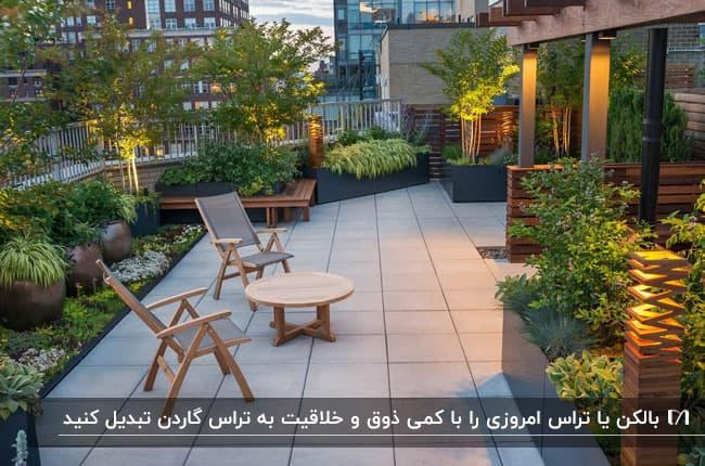 تصویر گرین تراس سرسبزی با نورپردازی های تقطه و میز و صندلی چوبی