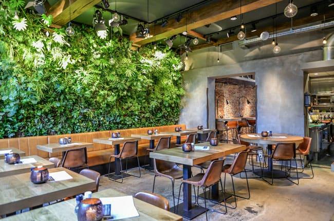 تصویر فضای داخلی رستورانی با میز و صندلی های چوبی و فلزی و یک دیوار سبز مستطیلی