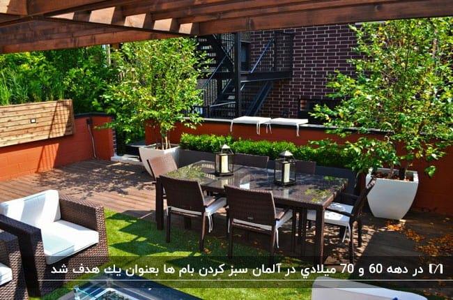 میز و صندلی و مبلمان حصیری قهوه ای با دشکچه های سفید در تراس سبزی با پرگولای چوبی