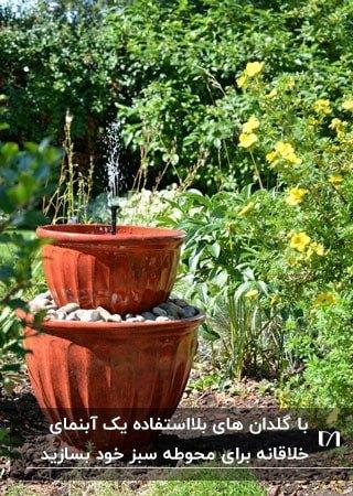 آبنمایی در حیاط با دو گلدان قهوه ای رنگ روی هم