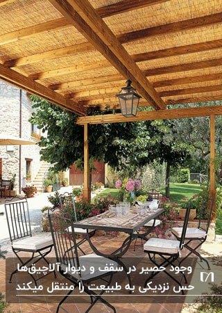 استفاده از حصیرها برای سقف آلاچیق باریکی با میز و صندلی های فلزی
